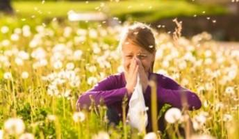 bambina in un prato con allergia